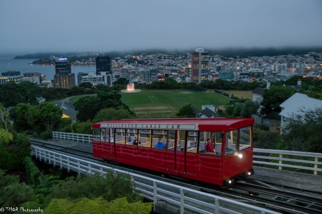 Red trolly on road with city in the background